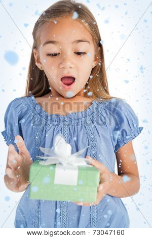 Composite image of Surprised little girl holding a wrapped gift with snow falling