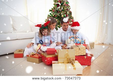 Young family unpacking Christmas presents against snow falling