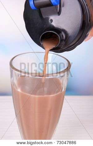 Shaker with protein shake and glass on table on bright background