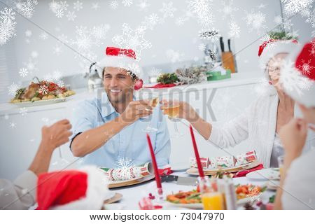 Happy family clinking their glasses of white wine against snowflakes