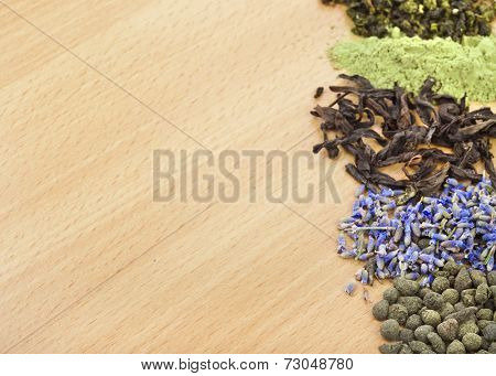 border frame of different heap dry tea on wooden table background, top view