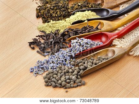assortment of dry tea addition in spoon scoops close up  on wooden table background