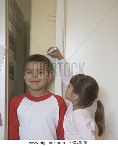 Sister measuring brother's height against wall