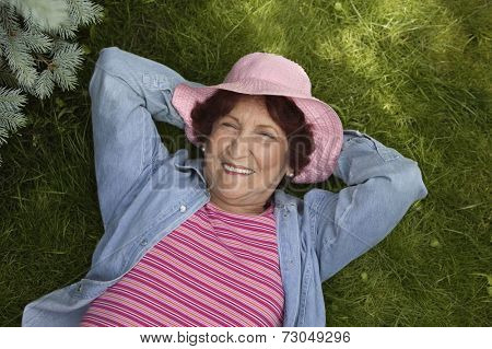 Portrait of senior woman laying in grass