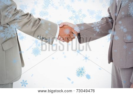 Side view of shaking hands against snow falling
