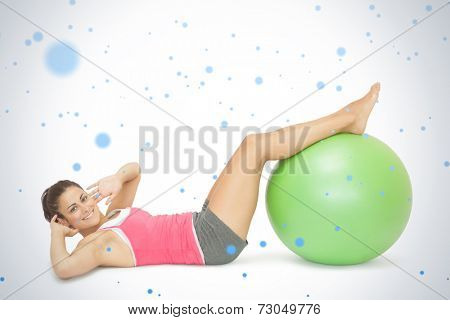 Smiling sporty brunette doing sit ups with exercise ball against snow falling