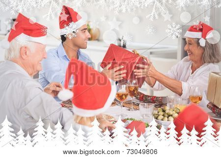 Happy family exchanging christmas gifts against fir tree forest and snowflakes