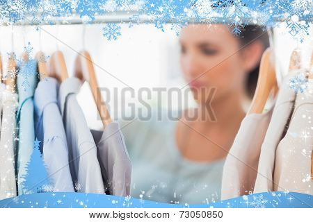 Fashion woman choosing clothes on clothes rail against snow