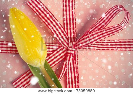 Composite image of snow falling against yellow tulip resting on girly present