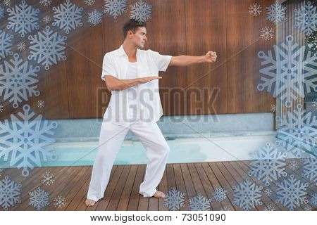 Handsome man in white doing tai chi against snowflake frame