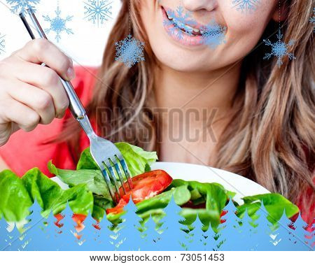 Close up of a delighted woman is eating a salad against snowflakes and fir trees in blue