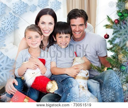 Portrait of a smiling family at Christmas time holding lots of presents against snowflake frame