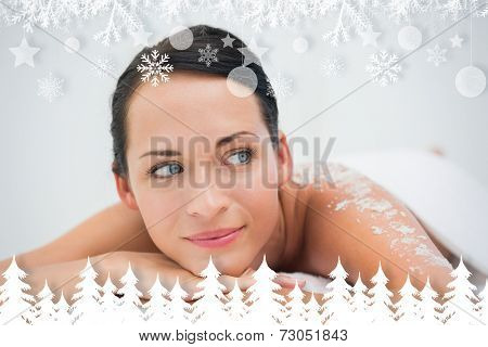 Peaceful brunette lying with salt scrub on back against fir tree forest and snowflakes