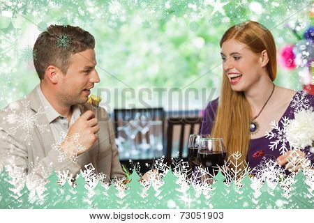 Composite image of cheerful couple eating together against snow