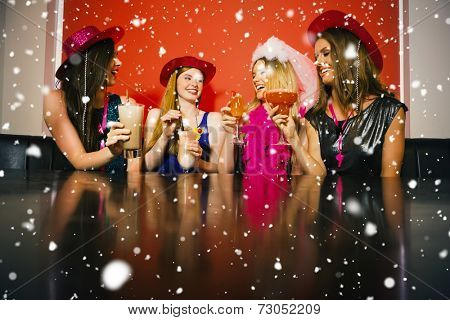 Attractive friends at a hen night drinking cocktails against snow falling