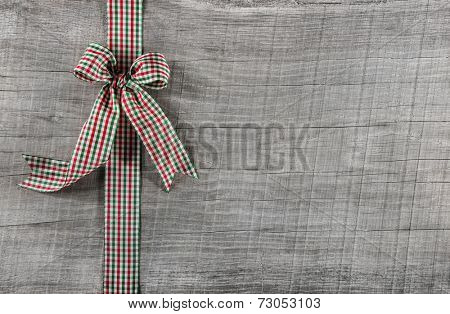 Red green checked ribbon on wooden background for christmas or other festivities.