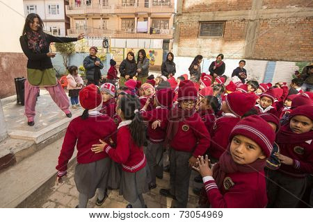KATHMANDU, NEPAL - DEC 22, 2013: Unknown pupils during dance lesson in primary school. In Nepal only 25% of girls attend schools and half of the children can reach the 5 grade.