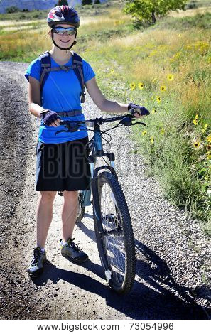Detail of woman mountain biking wearing blue exercise shirt and helmet
