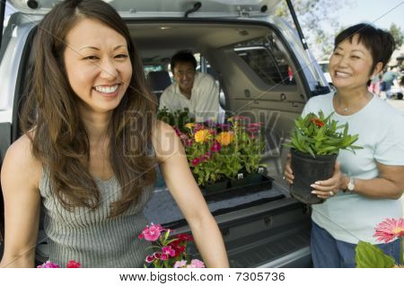Family Loading Flowers Into Back Of Suv, Portrait
