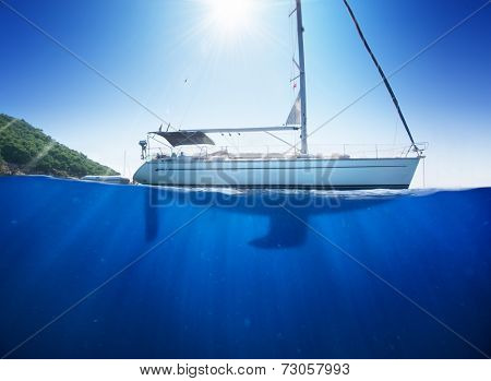 Amazing sunlight seaview to sailboat in tropical sea with deep blue underneath splitted by waterline