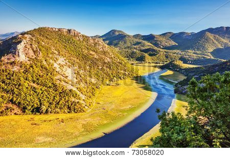 Sinuous river flowing through mountains. Natural park. Dramatic scene. Rijeka Crnojevica. Located near Skadar Lake, Montenegro, Europe. Beauty world.