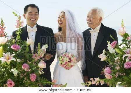 Bride and groom with father outdoors in Formal Clothing