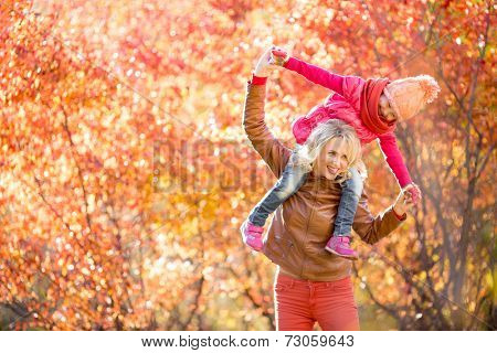 Happy mother and kid having fun together outdoor in autumn or fall park.