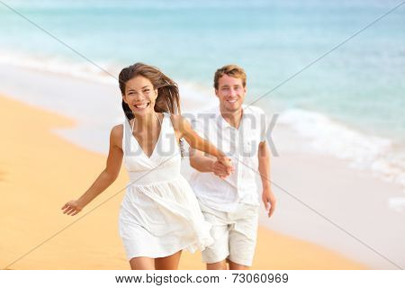 Couple on beach running having fun laughing in elegant casual beach wear. Happy multicultural multi-ethnic young lovers and friends by ocean on summer vacation holidays travel. Woman and man.