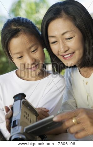 Mother and Daughter in backyard Looking at Video Camera Screen