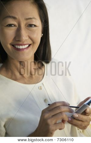 Middle Aged Asian Woman using PDA portrait