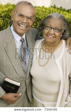 Smiling Senior Christian Couple in garden holding Bible portrait