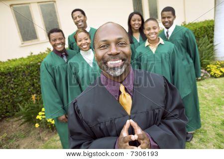 Minister in church garden gospel choir in background portrait