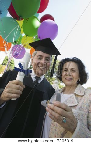 Senior graduate receiving present from wife outside low angle view