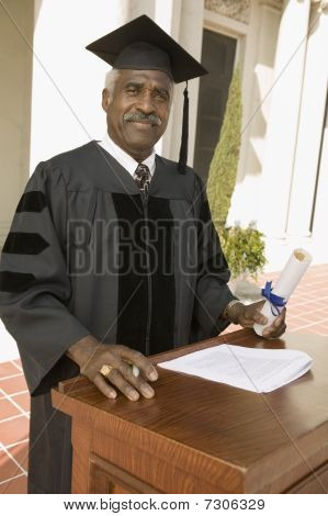 Ethnic Senior graduate at podium outside portrait