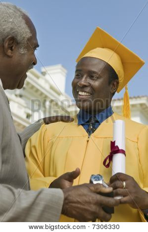 Graduate receiving present from father outside university