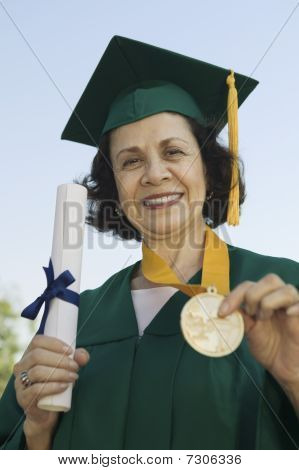 Senior Graduate holding diploma and medal outside portrait
