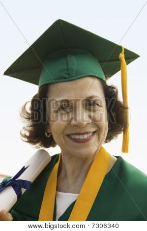 Smiling Senior Graduate holding diploma outside portrait