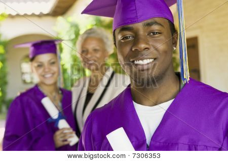 Graduate outside with second graduate and grandmother behind portrait