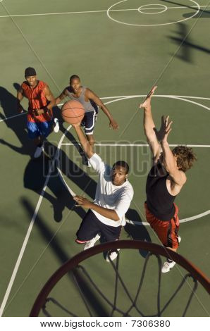 Man shooting basketball on court elevated view action shot