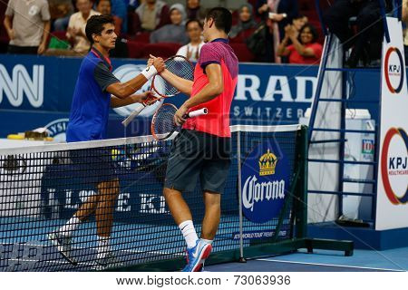 SEPTEMBER 23, 2014 - KUALA LUMPUR, MALAYSIA: Bernard Tomic (red) congratulates Pierre-Hugues Herbert for his first round win at the Malaysian Open Tennis 2014. This is an ATP sanctioned tournament.