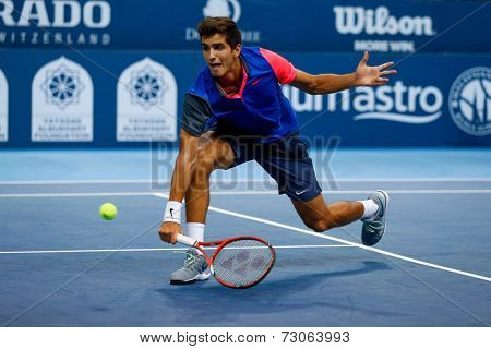 SEPTEMBER 23, 2014 - KUALA LUMPUR, MALAYSIA: Pierre-Hugues Herbert of France makes a backhand volley in his first round match at the Malaysian Open Tennis 2014. This is an ATP sanctioned tournament.