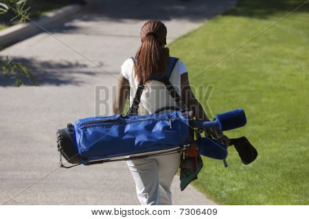 Woman carrying golf club bag rear view