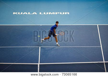 SEPTEMBER 25, 2014 - KUALA LUMPUR, MALAYSIA: Pierre-Hugues Herbert of France makes a forehand return in his match at the Malaysian Open Tennis 2014. This is an ATP sanctioned tournament.