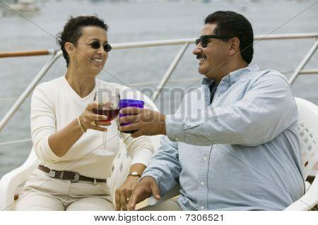 Постер, плакат: Средняя пара возрасте поджаривания напитки на яхте, холст на подрамнике
