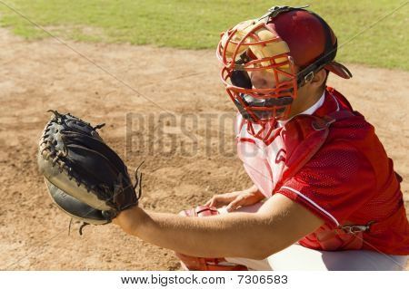 Baseball Catcher Crouching On Baseball Field