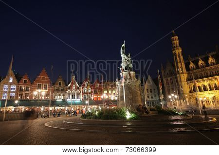BRUGES, BELGIUM - SEPTEMBER 6, 2014. The houses of the Grote Markt square at dusk on September 6, 2014. The historic city centre of Bruges is a prominent World Heritage Site of UNESCO