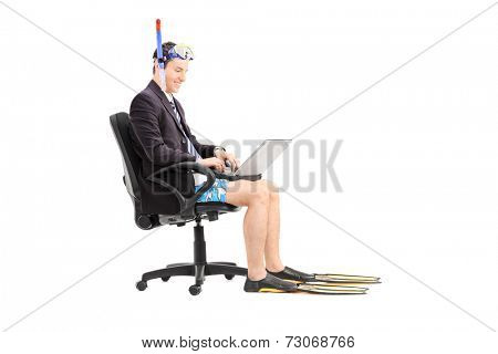 Businessman with a snorkel working on laptop seated in an office chair isolated on white background