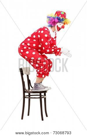 Male clown preparing to jump off a chair isolated on white background