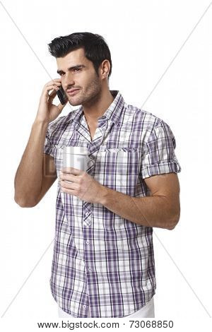 Handsome young man talking on mobilephone, drinking coffee, looking away.