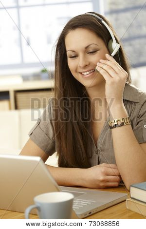 Young woman having video call, using laptop and headset, smiling.